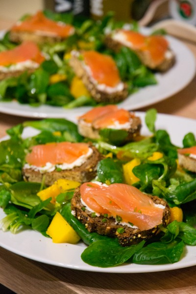 Tartines de pain noir au saumon fumé, salade de mâche et mangue